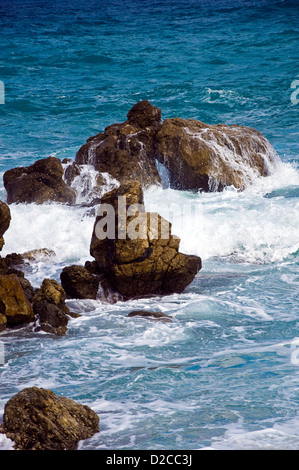 Wave breaking on rocky shore - Stock Photo
