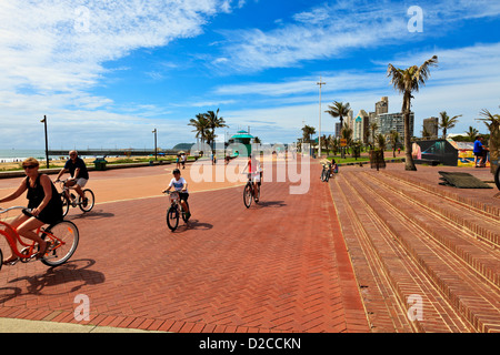 Durban South Africa. A Durban family cycles along the promenade along the Golden Mile promenade on the beach front. - Stock Photo