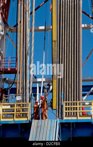 Onshore oil and gas exploration site. Wire line tools being lifted up to rig platform floor before logging. Kurdistan - Stock Photo