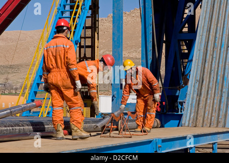 Onshore oil and gas exploration site. Making up wire line logging tools before lifting up to rig platform floor. - Stock Photo