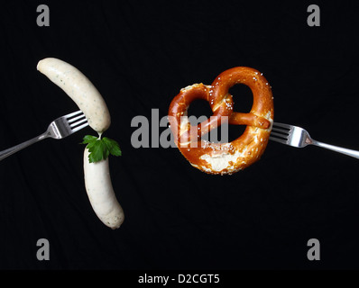 Stylish still life wiht bavarian veal sausage and pretzel on two spoons - Stock Photo