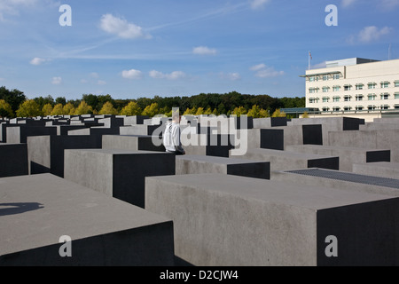 A young man walks through the Memorial to the Murdered Jews of Europe, Berlin - Stock Photo
