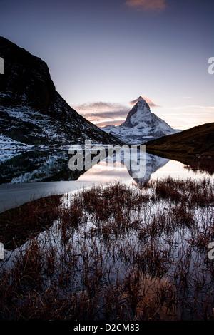 Matterhorn from Riffelsee mountain lake after sunset. Zermatt, Switzerland - Stock Photo