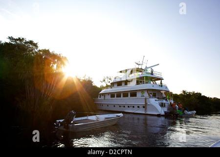 Sunset behind a luxury fishing yacht, on the Rio Negro in the Brazilian Amazon - Stock Photo