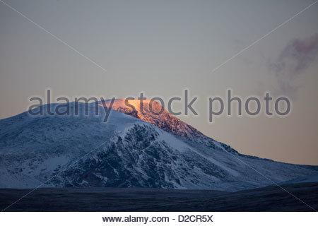 First light on Svanåtindan at Dovrefjell, Norway. - Stock Photo