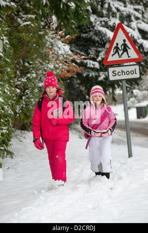 Children walking from school along a snow covered road Hampshire UK - Stock Photo