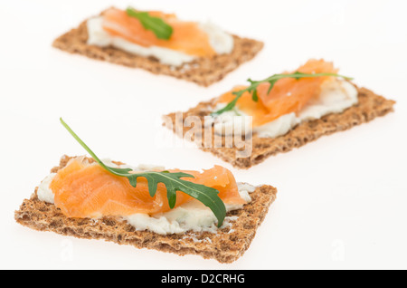 Crispbread with cream cheese and smoked salmon - studio shot with a white background and shallow depth of field - Stock Photo