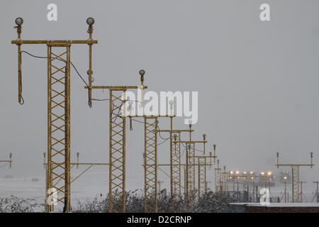 Runway cleaning trucks seen at City Airport behind a line of Air traffic control lights - Stock Photo