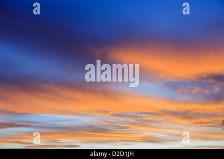 Fiery September evening skyscape with clouds lit by the orange sunset against a darkening blue sky at sundown. England - Stock Photo