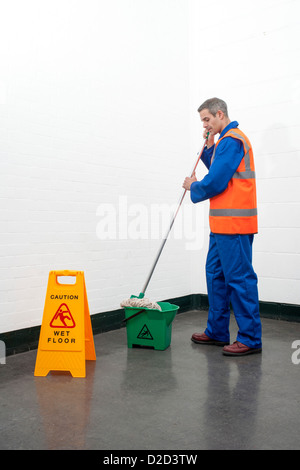MODEL RELEASED Mopping floor Man mopping a floor next to a caution sign - Stock Photo