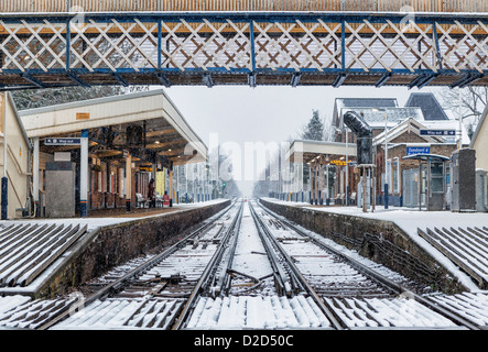 Empty Platforms, rail tracks and pedestrian bridge of the Strawberry Hill Rail Station after a winter snow fall - Stock Photo