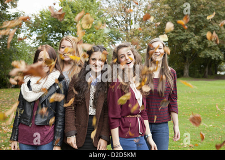 Girls playing in autumn leaves in park - Stock Photo