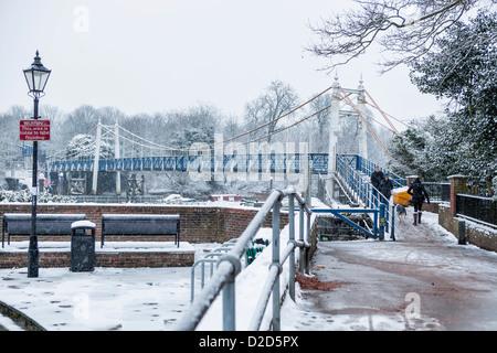 People crossing the snow covered pedestrian bridge at Teddington Lock in Winter- Greater London, UK - Stock Photo
