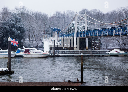 Boats moored next to the snow covered Pedestrian bridge at Teddington Lock  - River Thames, Greater London, UK - Stock Photo