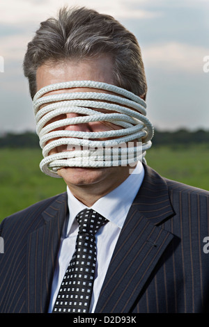 A mature businessman with rope wrapped around his face - Stock Photo