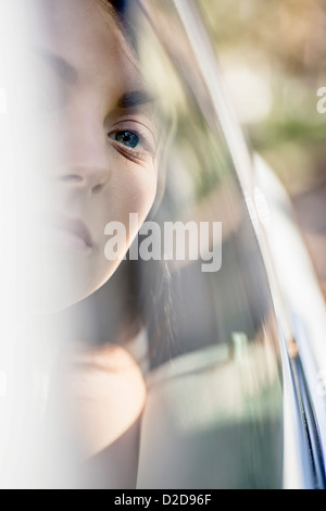 A young woman in a stationary car looking serenely out the window - Stock Photo