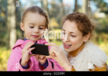 A young daughter showing her Mom something on a smart phone - Stock Photo