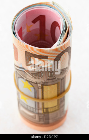 50 Euro note on a money roll of Euros rolled up with an elastic band on a white background to illustrate saving money concept. Europe