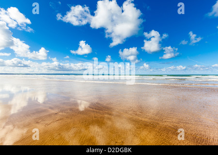 Empty beach with fluffy clouds reflected in the wet sand, Saunton Sands in North Devon, UK. - Stock Photo