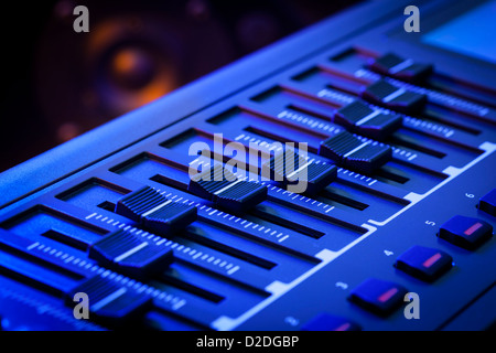 Close-up of a row of control faders on a MIDI controller Keyboard with a speaker out of focus in the background. - Stock Photo