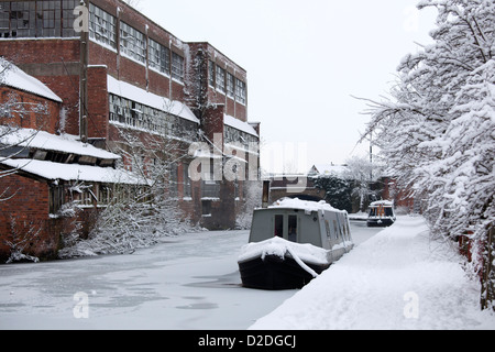A frozen canal boat sits on the Coventry canal in Atherstone, overshadowed by a unused factory on the Coleshill - Stock Photo