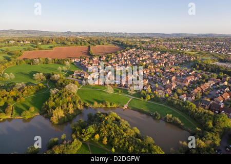 Aerial view of a rural English town next to a river and fields. - Stock Photo