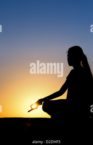 Sunset silhouette of an Indian girl meditating. Andhra Pradesh, India - Stock Photo