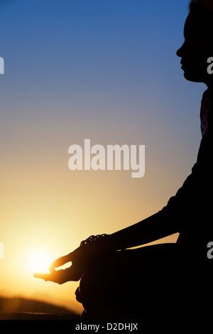 Sunset silhouette of an Indian girl meditating. Andhra Pradesh, India - Stock Photo