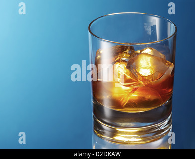 Whiskey glass on a blue background. - Stock Photo