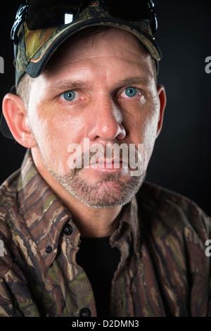 Close up headshot portrait of mature man wearing camouflage shirt and basecap, male, 40 years, Caucasian - Stock Photo