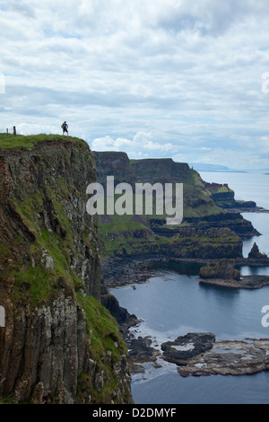 Walker on top of Benbane Head, on the Causeway Coast Way walking trail, County Antrim, Northern Ireland. - Stock Photo