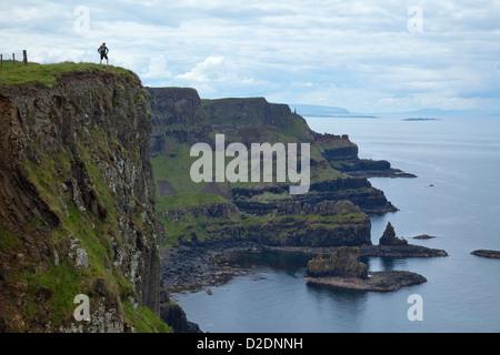 Walker on top of Benbane Head, on the Causeway Coast Way walking trail, County Antrim, Northern Ireland. - Stock Photo