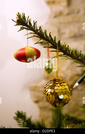 Vintage fabric and glass Christmas decorations hanging on a Nordmann Fir (Abies nordmanniana) Christmas tree. - Stock Photo