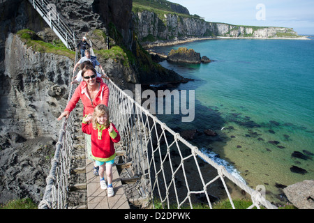 Woman and child crossing Carrick-a-rede Rope Bridge, County Antrim, Northern Ireland. - Stock Photo