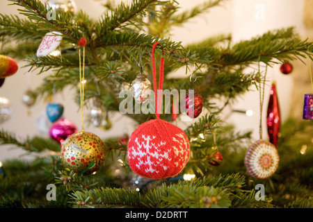 Christmas decorations hanging on a real Nordmann Fir (Abies nordmanniana) Christmas tree. Knitted and glass baubles. - Stock Photo