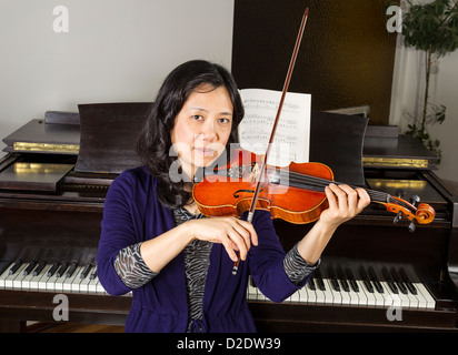 Mature Asian woman playing violin with old dark wooden piano in background - Stock Photo