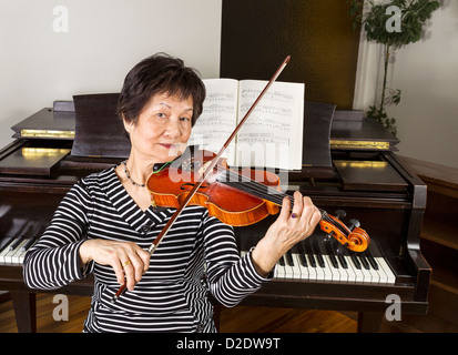 Senior adult woman playing the violin at home with piano in background - Stock Photo