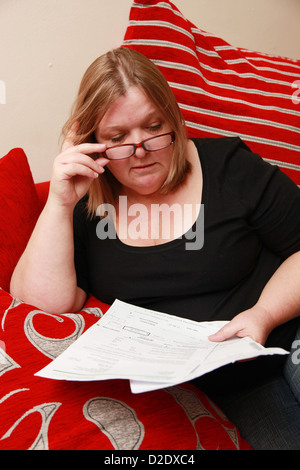Women looking at house hold bills - Stock Photo