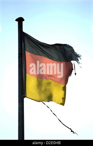 Berlin, Germany, the wind tore Germany flag on the mast - Stock Photo