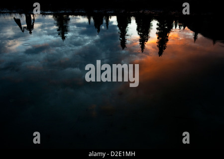 One man reflected upside down in a lake with colorful clouds and rain drops. - Stock Photo