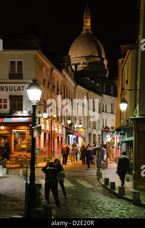 Café Le Consulat and basilica Sacre Coeur in Montmartre at night - Stock Photo