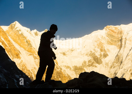 A trekker with alpenglow at sunrise on Annapurna South and Annapurna Fang, Nepelese Himalayas. - Stock Photo