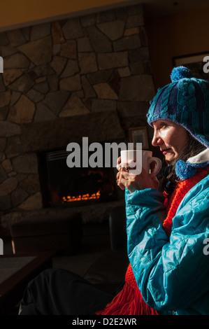 Woman enjoying a mug of hot chocolate near a fireplace in lodge in Crawford Notch, NH. - Stock Photo