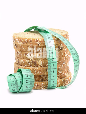 Fresh multigrain bread tied by green measuring tape - diet doncept. - Stock Photo