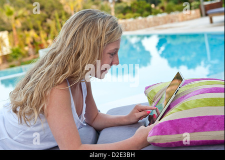 IPAD STREAMING DOWNLOAD iTunes FaceTime 4g abroad Teenage girl using a tablet iPad computer relaxing by luxury vacation - Stock Photo