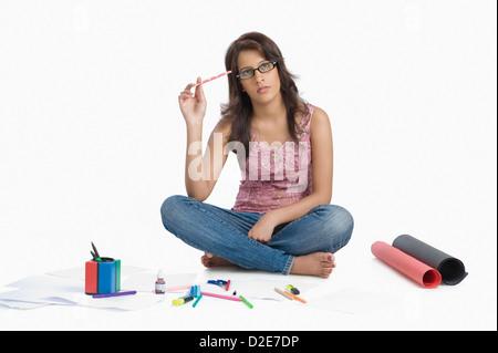 Female fashion designer sketching and thinking - Stock Photo