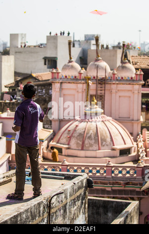 Boy flying a kite, Kite Festival or Uttarayan in Ahmedabad, Gujarat, India - Stock Photo