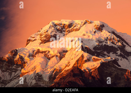 Alpenglow at sunset on Annapurna South, Nepelese Himalayas. - Stock Photo