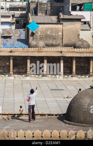 Boy flying a kite on the Jama Masjid, Kite Festival or Uttarayan in Ahmedabad, Gujarat, India - Stock Photo
