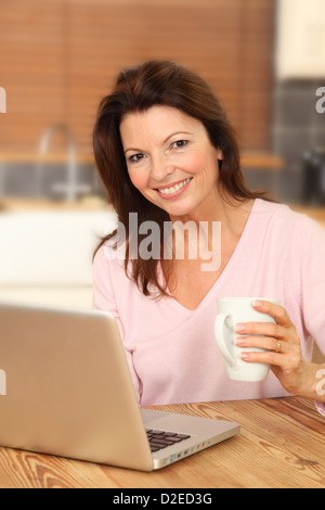 Attractive mature woman using a laptop, sitting at the kitchen table holding a white mug, smiling to camera. - Stock Photo